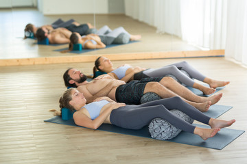 Fotomurales - Restorative yoga with a bolster. Group of young sporty attractive people in yoga studio, lying on bolster cushion, stretching and relaxing during restorative yoga. Healthy active lifestyle.