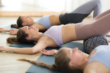 Fotomurales - Restorative yoga with a bolster. Group of three young sporty attractive women in yoga studio, lying on bolster cushion, stretching and relaxing during restorative yoga. Healthy active lifestyle.
