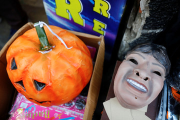 A pumpkin and a mask are pictured during Halloween celebrations in La Paz