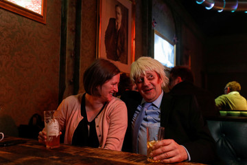 "A man dressed as Britain's Prime Minister Boris Johnson speaks to a woman attending the ""End of the World Party"" on the night Britain was due to leave the EU in London"