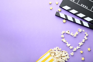 Clapper board with popcorn on purple background