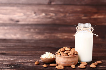 Wall Mural - Almond and milk in bottle on brown wooden table