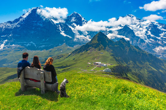 Tourists admire Eiger, Monch and Jungfrau mountains from summit of mountain Mannlichen, popular viewpoint in Swiss Alps, Switzerland.