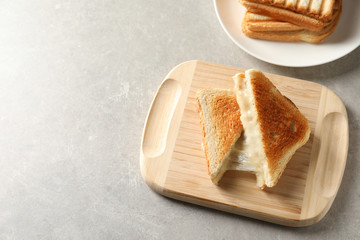 Wooden board with fresh cheese sandwiches on grey table, above view. Space for text