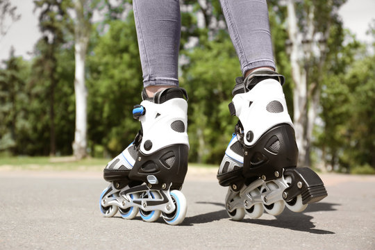 Woman with modern inline roller skates in city park, closeup
