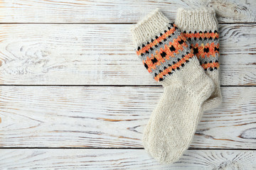 Fototapete - Warm knitted socks on white wooden background, flat lay. Space for text
