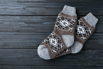 Fototapete - Warm knitted socks on black wooden background, flat lay. Space for text