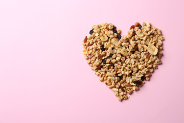 Heart made of ingredients for homemade healthy granola bars on pink background, flat lay. Space for...