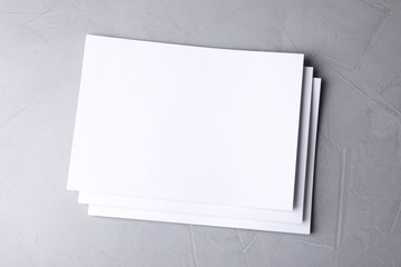Blank paper sheets on light grey stone background, top view. Mock up for design