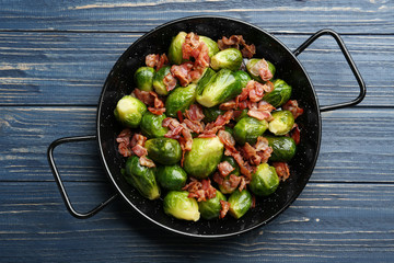 Tasty roasted Brussels sprouts with bacon on blue wooden table, top view