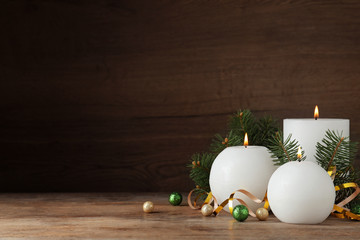 Fotobehang - Beautiful Christmas composition with burning white candles on wooden background. Space for text