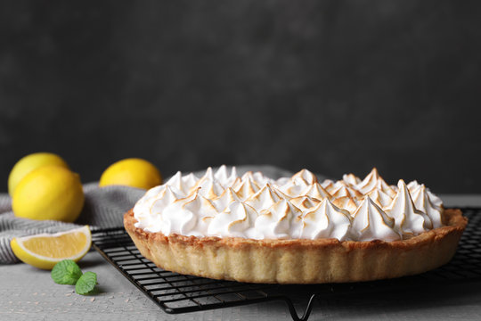 Cooling rack with delicious lemon meringue pie on grey table