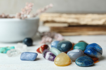 Pile of different gemstones on white wooden table. Space for text
