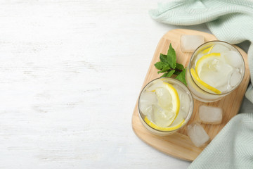 Glasses of cocktail with vodka, ice and lemon on white wooden table, top view. Space for text