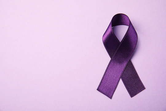 Purple ribbon on pink background, top view with space for text. Domestic violence awareness
