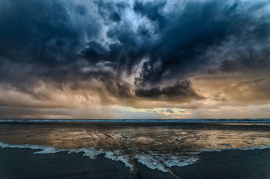 Breathtaking shot the ocean covered by the dark cloudy sky with the sun hidden behind the clouds