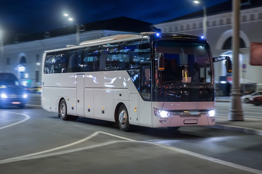 Tourist bus moves at night on a city street