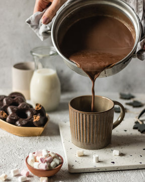 Cup of hot chocolate poured on bright background with cookies and marshmllow