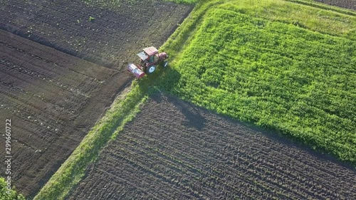Wall mural Tractor on a plowed agricultural field on a sunny day. 4K video, 240fps, 2160p.