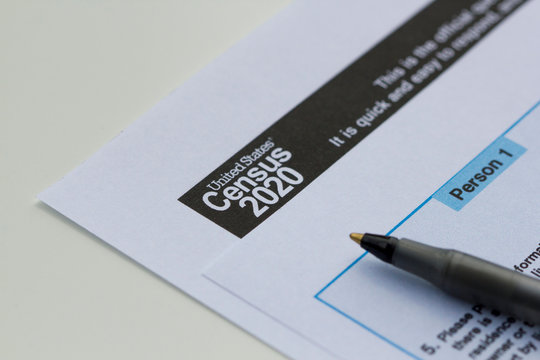 United States Census 2020 form informational copy and a ballpoint pen on a white background