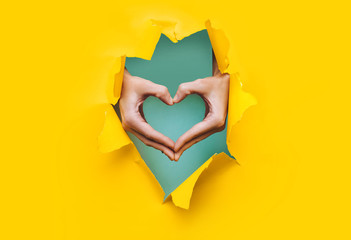 Female hands show a heart symbol through the torn holes of a yellow and green paper background. Creative art, copy space. Concept of love.