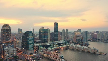 Fototapete - Drone footage with camera rotation and slow panning rotation in front of Jersey City skyline at sunset.