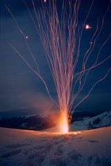Close-up of fireworks on top of a snowy mountain at night in winter. Real grain scanned film.
