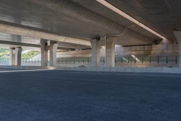 Close-up of asphalt pavement and pier under concrete overpass
