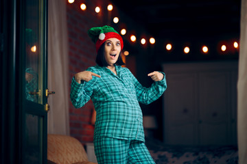 Funny Pregnant Woman Celebrating Christmas in Pajamas