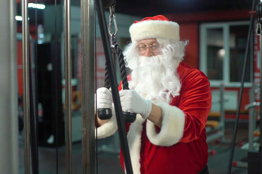 Santa Claus training at the gym on Christmas Day. Santa Claus working doing exercises at triceps.