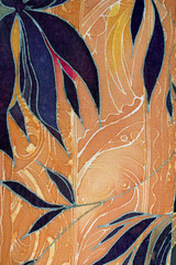 Orange and dark blue painting on fabric abstract background with flowers and leaves