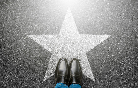 Success in business design concept. Businessman standing on street road background. Top view. Selfie of feet in black leather shoes and white star symbol on pathway floor. New talent or champion.