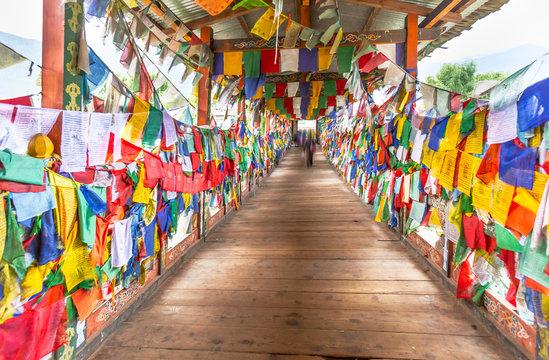 Colorful Buddhist prayer flags on wooden bridge walk way to Monastery in Thimpu, Bhutan