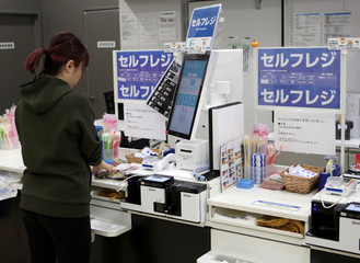 A shopper checks out at an unmanned cash register with using her mobile phone at convenience chain store Lawson in Tokyo