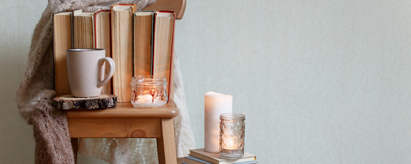 hygge and cozy home concept - books, cup of coffee or hot chocolate and candles, seasonal autumn...