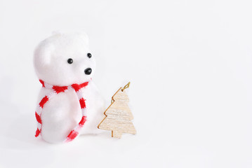 White winter Christmas decoration toy bear with striped scarf near wooden design fir tree symbol decor white background with free blank copy text space in the right Left oriented picture greeting card