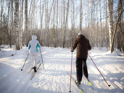 An elderly couple resting in the park on cross-country skis. The concept of health preservation at any age.