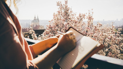 Girl enjoying sunny day in blooming garden on hill top over Prague. Cropped female hands writing in notepad or artist drawing sketch, camera focused at scenic city view and flowering magnolia tree. Fotomurales