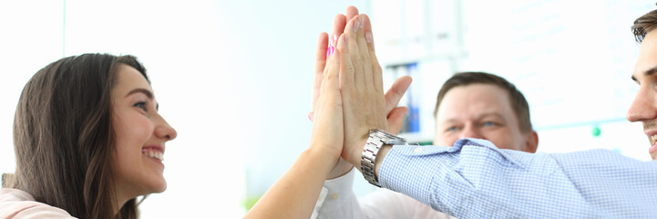 Portrait of pretty female manager in office performing friendly gesture with joyful coworkers. Businesspeople doing high five. Teamwork concept. Blurred background