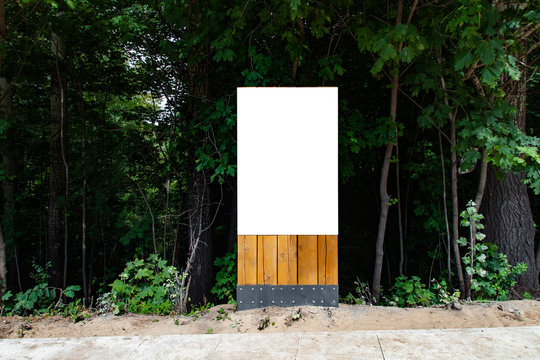 Blank vertical billboard on green grass in park to place your logo or advertising on it on wooden stand