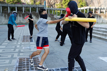 Masked participants spar with foam sticks during a self-defence class organised by a student union at the Chinese University of Hong Kong, in Hong Kong, China
