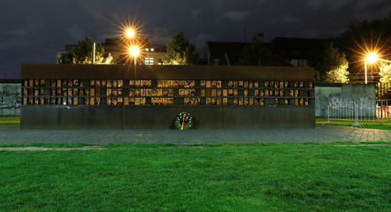 A long exposure picture shows photographs of victims killed at the Wall at the Berlin Wall memorial on Bernauer Strasse at night in Berlin
