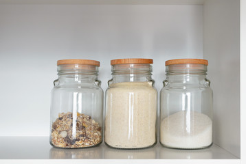 Glass jar with various product for breakfast: sugar, semolina and muesli. Food products in the kitchen storing. Horizontal composition