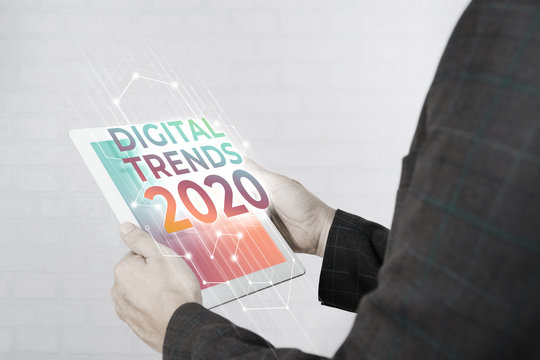 Man hand holding white tablet with Digital Trends 2020 on screen. New trends digital marketing, business and technology concept.