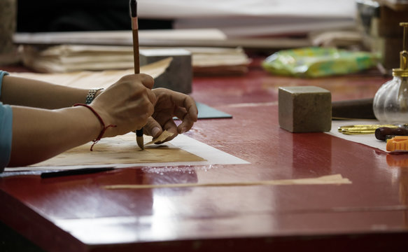 Traditional Chinese book and calligraphy restorer laboratory. Master hands at work close-up.