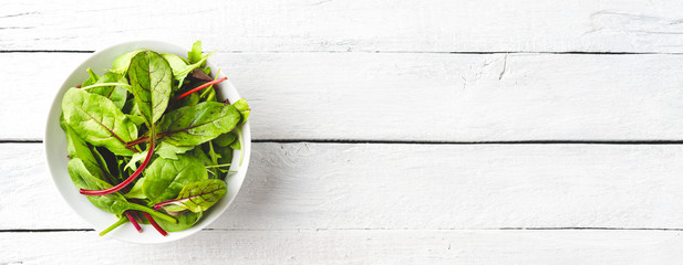 Overhead shot of fresh green salad with spinach, arugula and beetroot leaves in bowl on white wooden background with copyspace. Banner