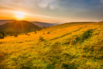Poster de jardin Melon Landscape sunset in mountains with forest, green grass and big shining sun on dramatic sky