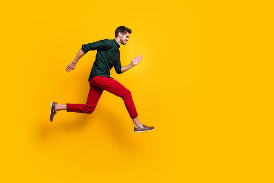 Full body profile side photo of positive cheerful funky guy hear about wonderful black friday sales jump run want be first wear casual style outfit isolated over yellow color background