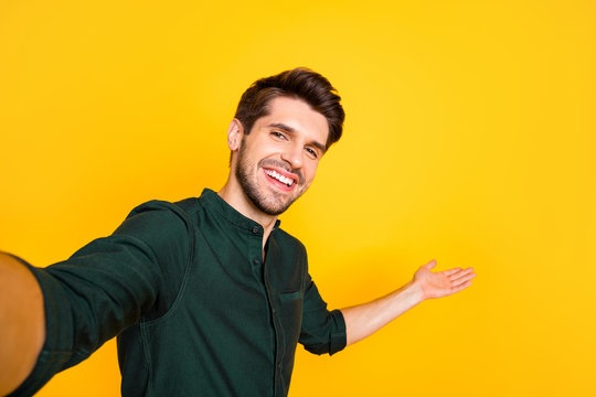 Close up photo of positive cheerful guy hold hand take selfie invite his blogging followers to perfect rest relax through video call wear casual style outfit isolated over yellow color background