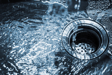 stream of clean water pouring into a steel sink in the kitchen. Toned image